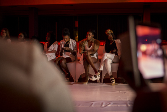 Young women watch models on the catwalk in Blacktown, Sydney. The  fashion show by Australian South Sudanese designers D&M, Deng and Mayom, toured nationally this year.