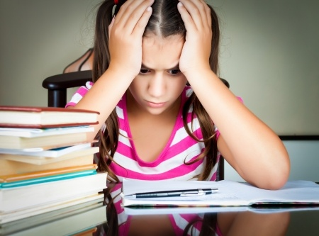 Young female foster care student is frustrated because she does not understand her homework.