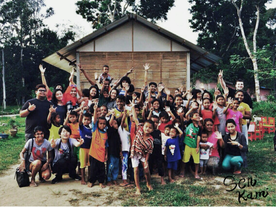 The Orang Asli children from Rasau Village seen here posing for a photo outside their community school with some of the Senikami volunteers