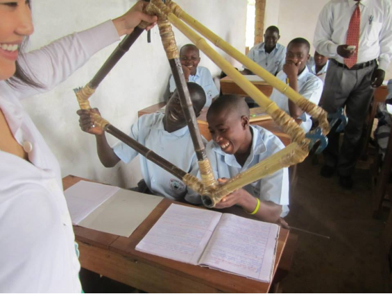 Merry Walker in Uganda, sharing a Bandha Bikes frame with classroom students.