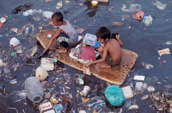 Boys on a home-made raft in a sea of plastic
